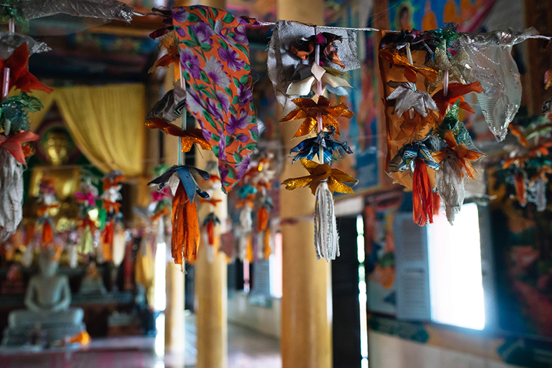 Colourful flags and decorations hanging inside bright painted Buddhist temple in Siem Reap Cambodia.