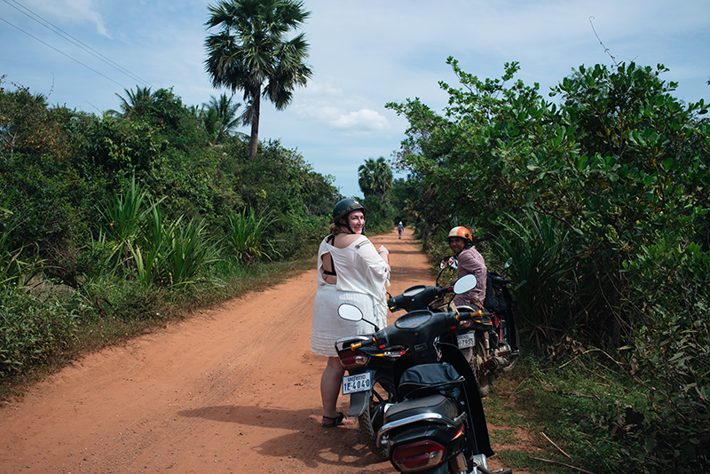 Motorbiking through the Siem Reap countryside in Cambodia on a Honda Dream with Khmer Ways. Dusty red orange sand roads.