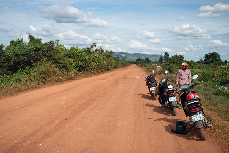 Motorbiking throught the Siem Reap countryside in Cambodia on a Honda Dream with Khmer Ways. Dusty red orange sand roads.