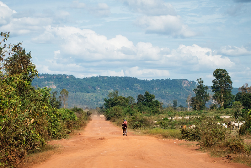 Countryside landscape in Siem Reap Cambodia, dusty sand roads and local on bike.