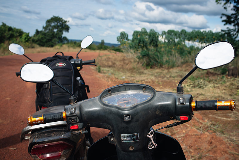 Motorbiking throught the Siem Reap countryside in Cambodia on a Honda Dream. Dusty red orange sand roads.