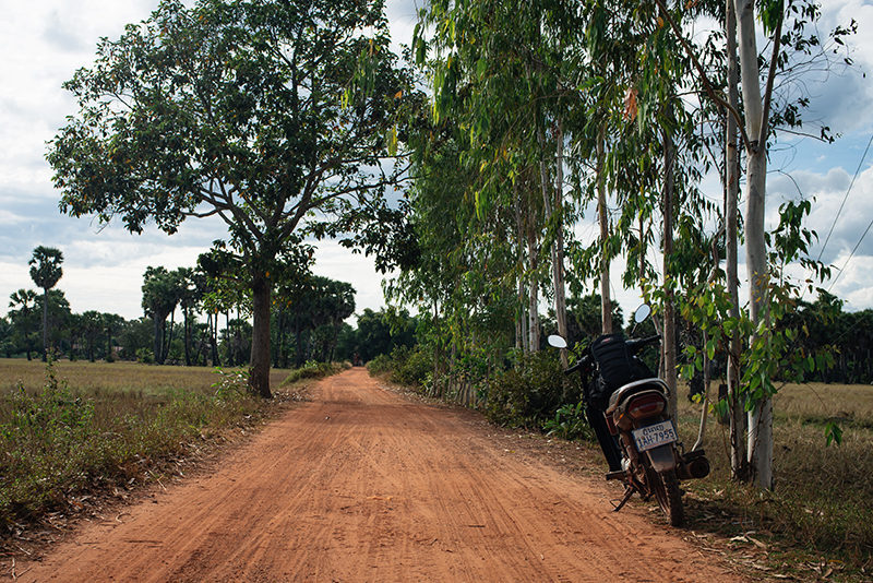 Motorbiking through the Siem Reap countryside in Cambodia on a Honda Dream. Dusty red orange sand roads.