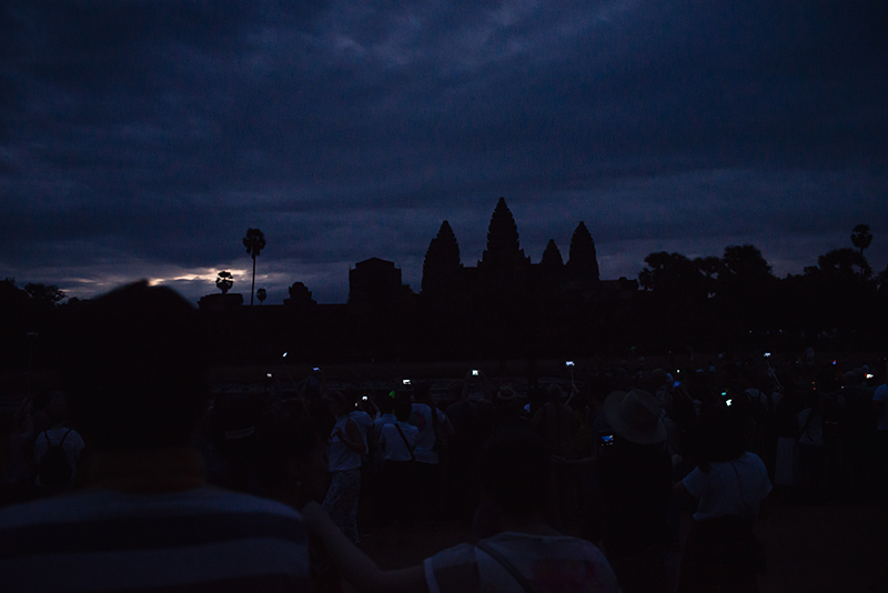 Crowd with mobile phones in the dark waiting for sunrise at Angkor Wat temple complex Siem Reap Cambodia.