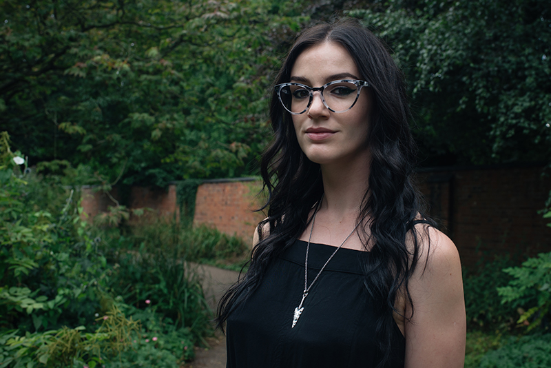 Fashion blogger Stephanie of FAIIINT wearing IOLLA Muir smoke tortoise cat eye frames glasses, Toilworn arrowhead pendent necklace. Portrait, outfit details.