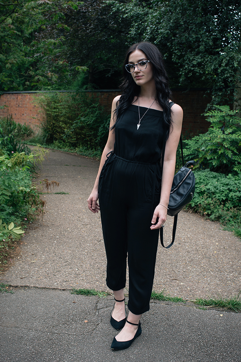 Fashion blogger Stephanie of FAIIINT wearing Warehouse jumpsuit, IOLLA Muir smoke tortoise frames glasses, Topshop pointed flats, Toilworn arrowhead necklace, New Look backpack. All black everything, casual street style outfit.