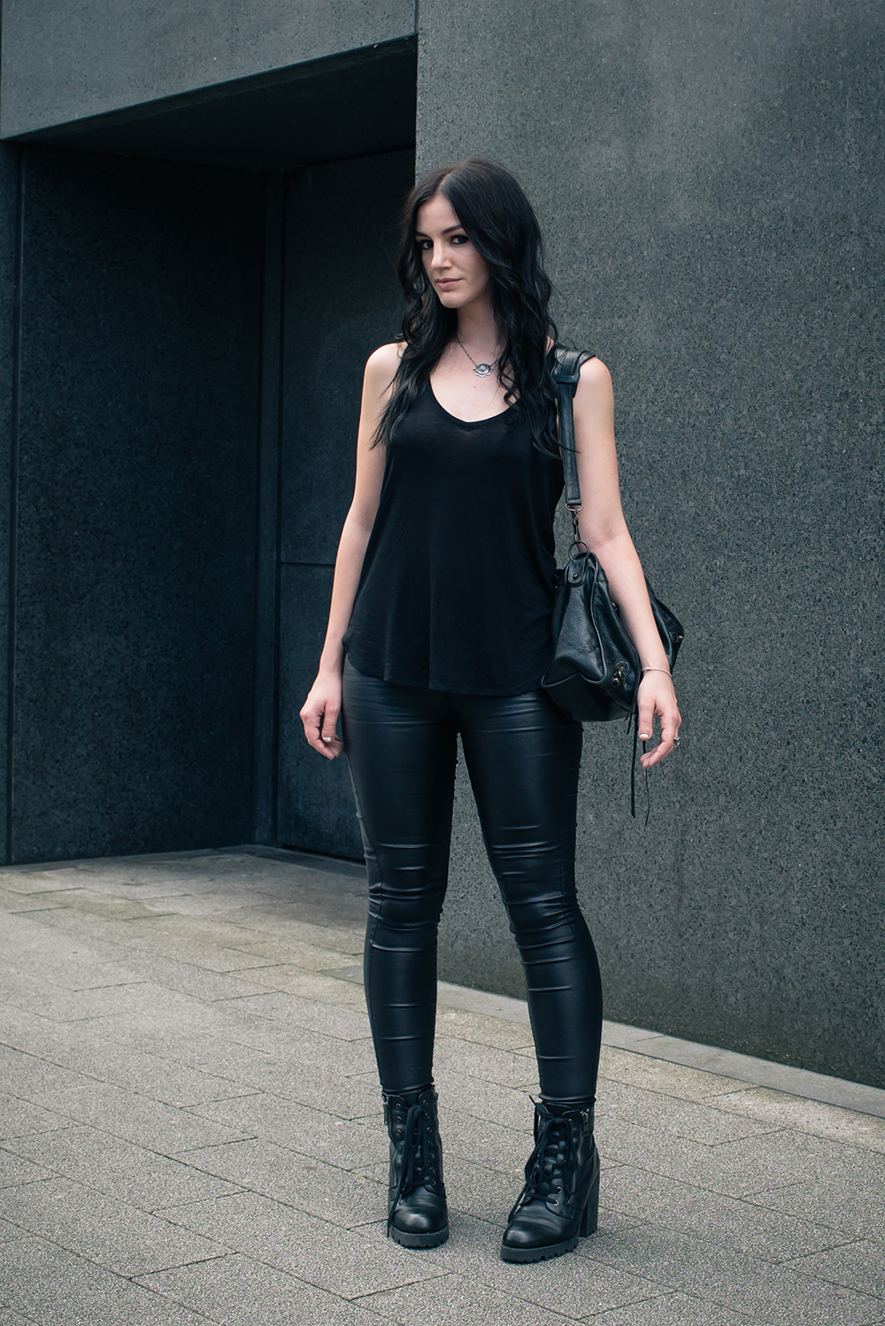 Fashion blogger Stephanie of FAIIINT wearing H&M black coated skinny jeans and tank top, ASH poker lace up ankle boots, Balenciaga city bag. All black simple dark street style outfit.