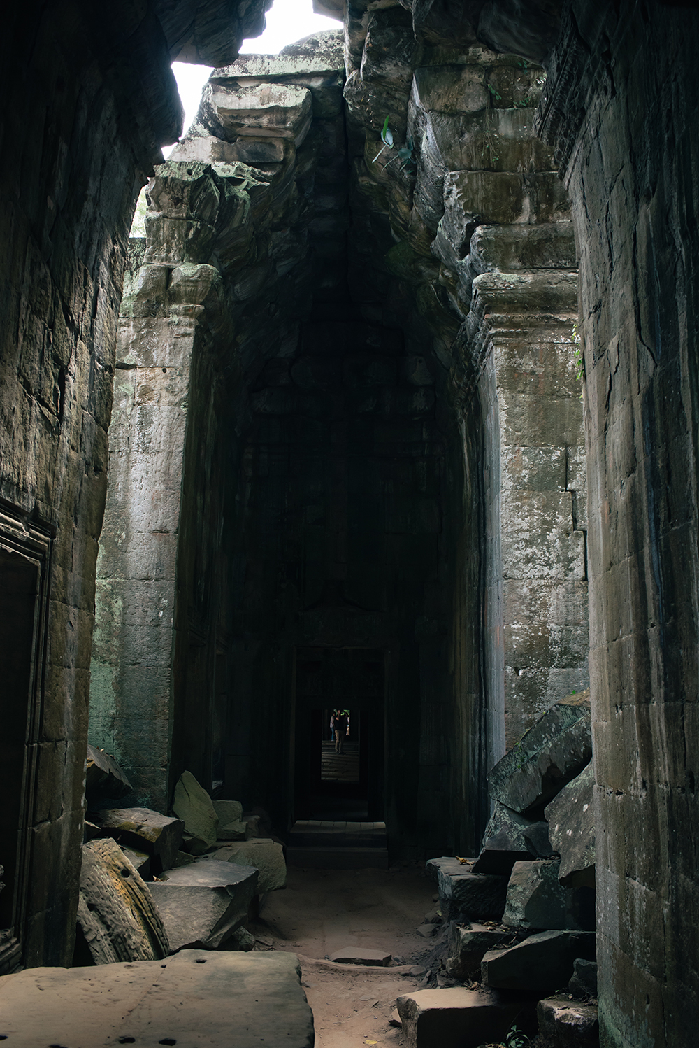 Ta Prohm temple arch hallway Siem Reap Angkor Cambodia. Crumbling ruins reclaimed by nature and overgrown with trees and plants.