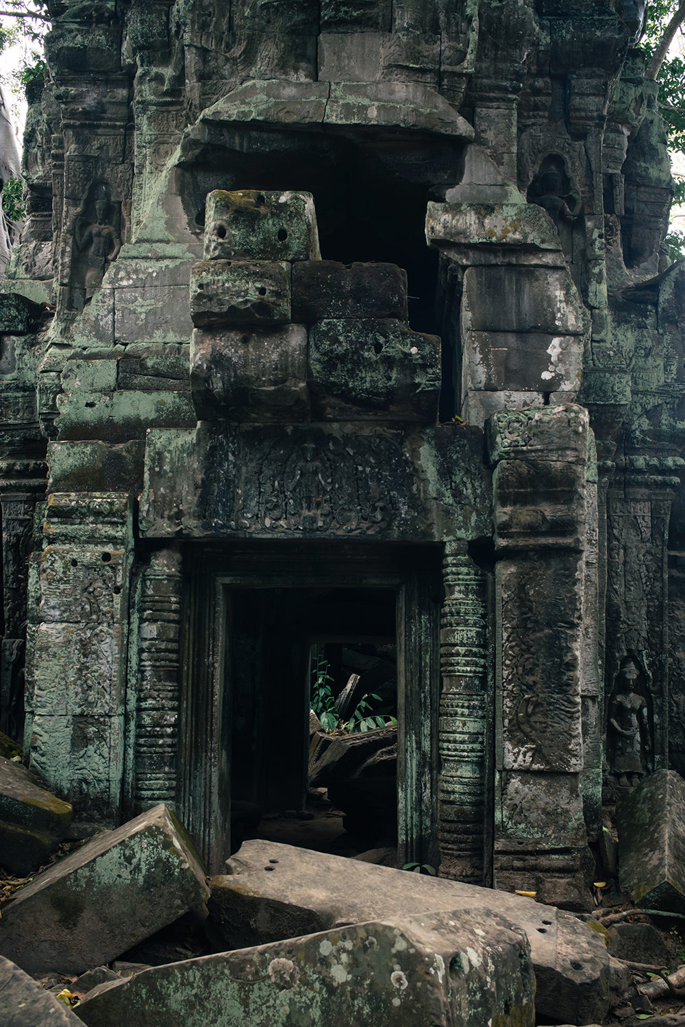 Ta Prohm temple doorway Siem Reap Angkor Cambodia. Crumbling ruins reclaimed by nature and overgrown with trees and plants.