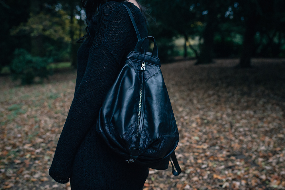 Fashion blogger Stephanie of FAIIINT wearing H&M black asymmetric knit jumper, Topshop backpack. All black autumn outfit details..