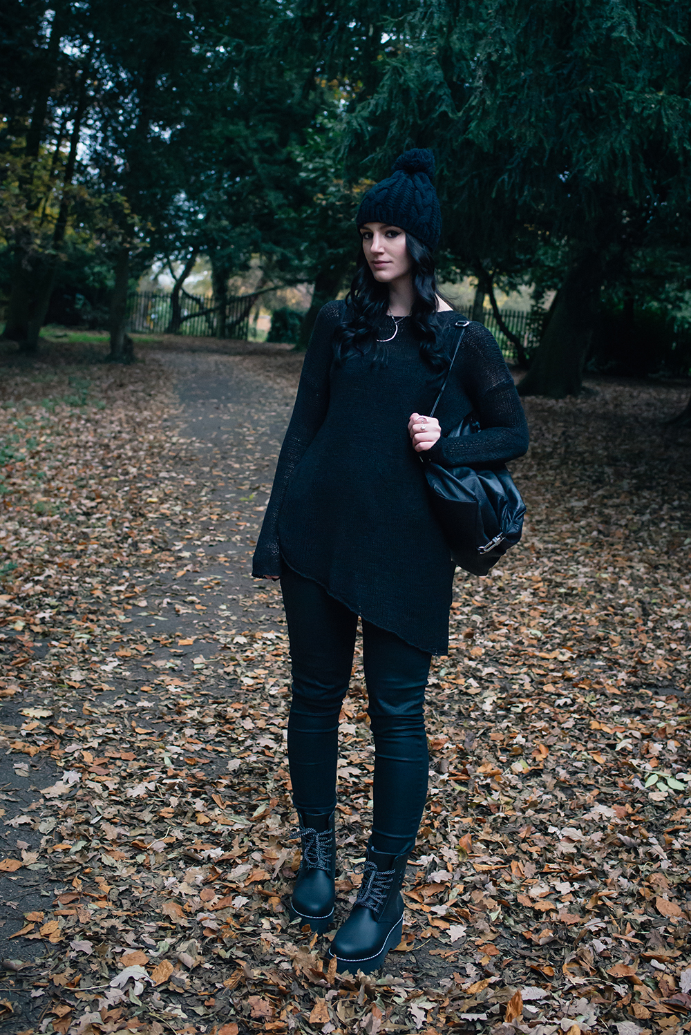 Fashion blogger Stephanie of FAIIINT wearing pom pom beanie hat, H&M black asymmetric knit jumper, coated skinny jeans, Dos61 high rubber boots, Topshop backpack. All black autumn outfit.