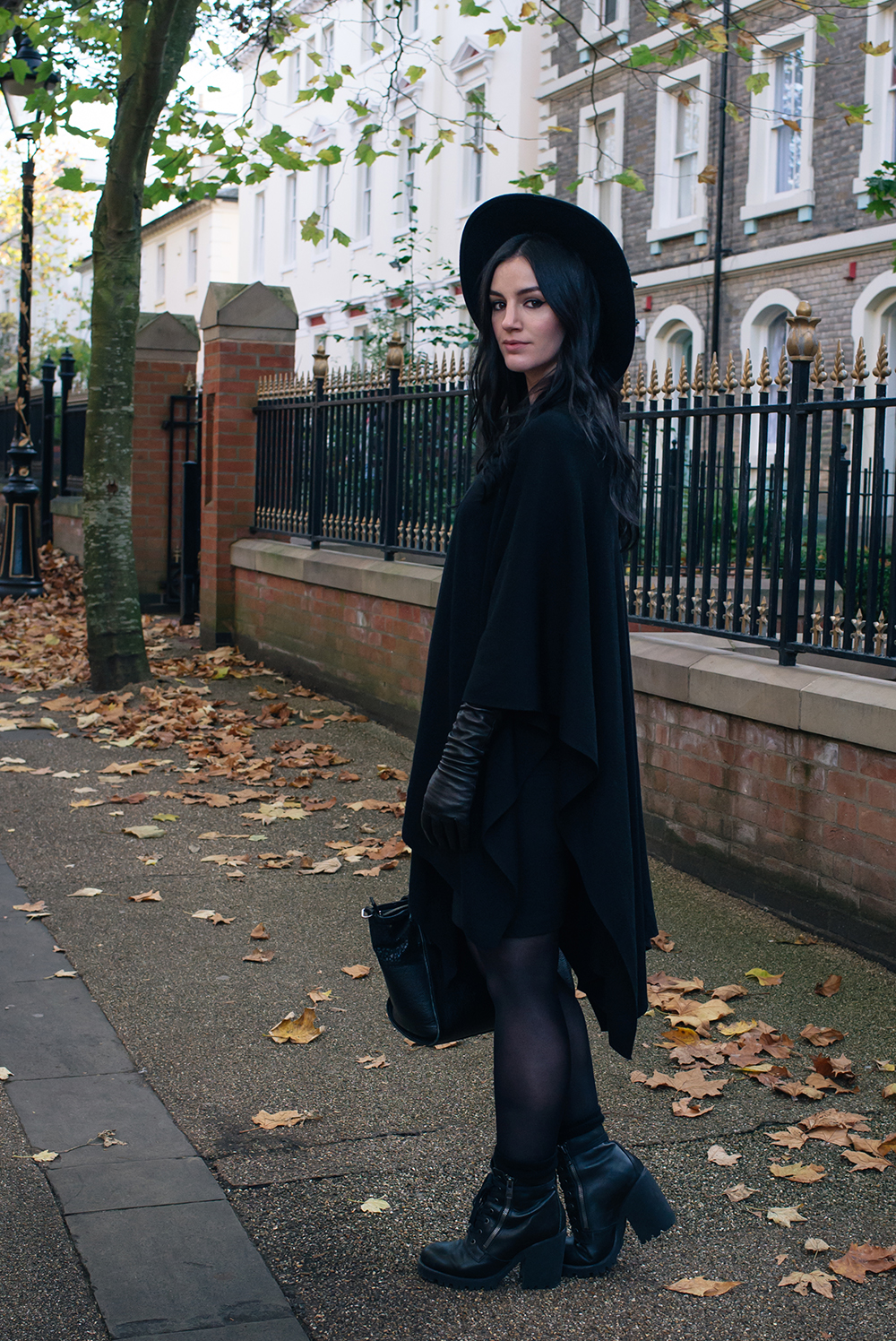 Fashion blogger Stephanie of FAIIINT wearing ASOS cape, H&M wide brim fedora, Black elbow high leather gloves, ASH poker lace up boots. Gothic style all black autumn outfit.