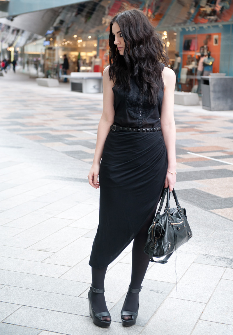 Fashion blogger Stephanie of FAIIINT wearing AllSaints Sleeveless Shirt, River Island Draped Asymmetric Skirt, Skin by Finsk Wedge Sandals, Topshop Studded Belt, ASOS Spiked Bangle, Balenciaga City bag. All black, dark, gothic, street style.