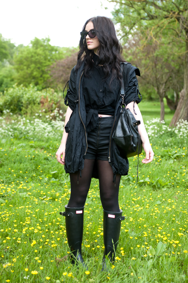 Fashion blogger FAIIINT wearing Topshop parka & shorts, ASOS tied shirt, black Hunter Wellies, AllSaints sunglasses, Balenciaga City bag. Festival inspired outfit, all black.