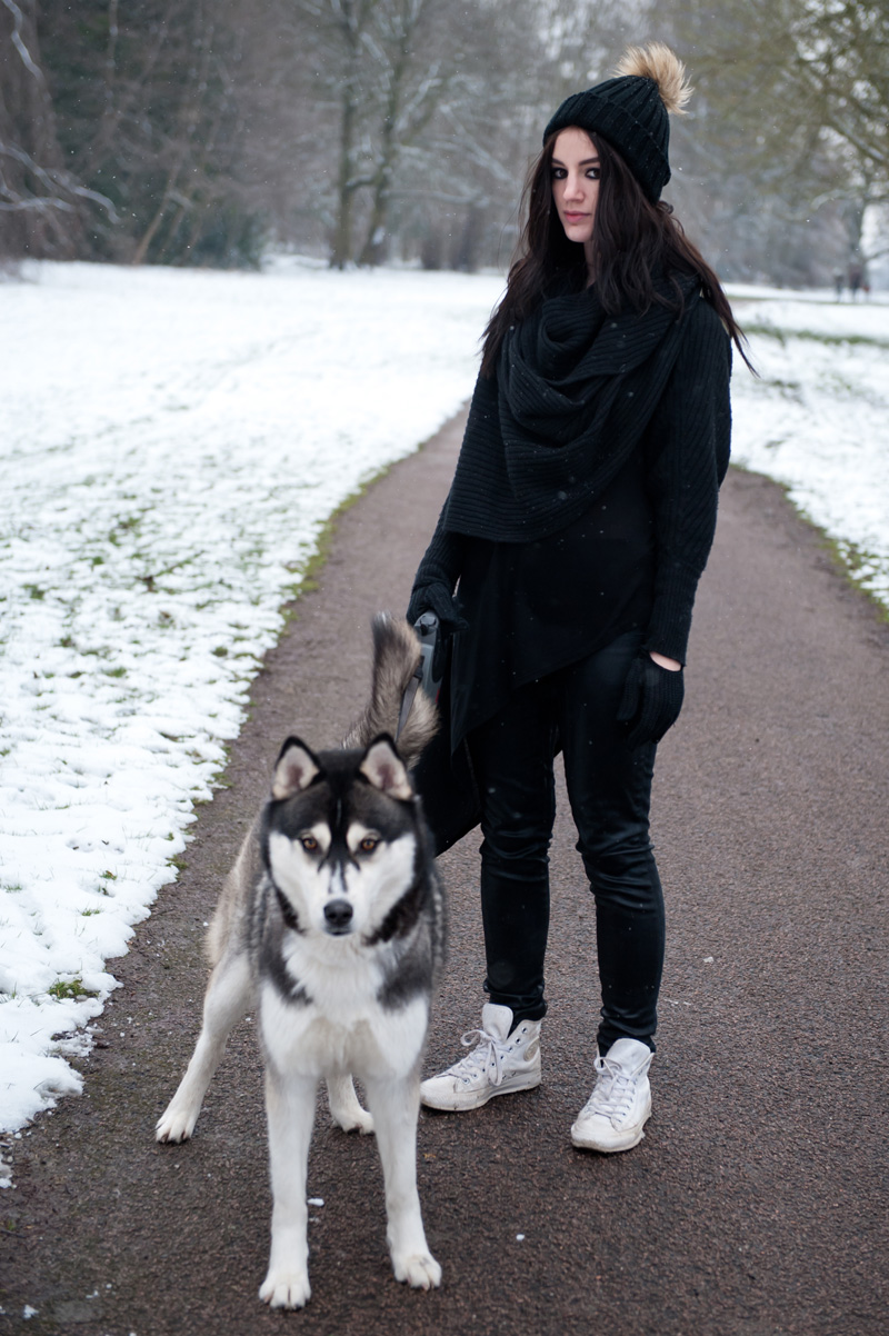 Fashion Blogger FAIIINT wearing AllSaints chunky draped knitted wrap cardigan, Nelly fur pom pom beanie, Topshop Asymmetric top, Topshop Unique coated jeans, white leather Converse hi-tops. Black outfit in the snow, snowing in the park with Siberian Husky puppy Nico.