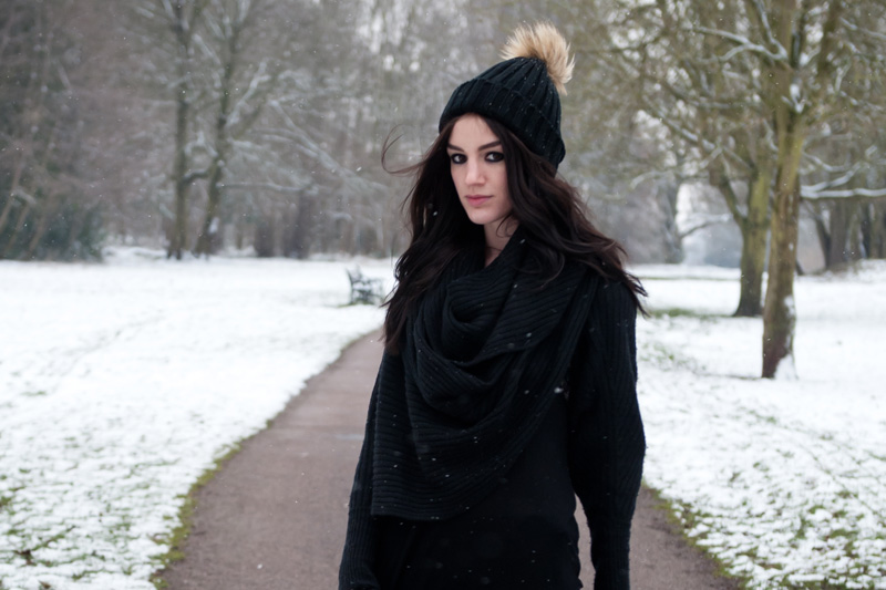 Fashion Blogger FAIIINT wearing AllSaints chunky draped knitted wrap cardigan, Nelly fur pom pom beanie, Topshop Asymmetric top. Black outfit in the snow, snowing in the park.