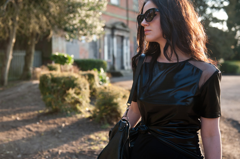 Fashion blogger Stephanie Brown of FAIIINT wearing MeeMee wet look cut out tee, River Island asymmetric skirt, Rick Owens wedges, Balenciaga city, AllSaints cateye sunglasses. Spring Summer gothic street style. All Black.